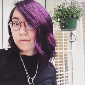 selfie of Amy Li; she has short purple hair, wears wide-framed glasses, and wears a black cotton dress with a silver necklace